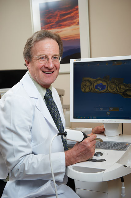 Dr. Stuart Ross working with 3D imaging technology and smiling at City Smiles DC.